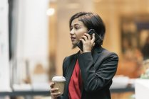 Young asian business woman with coffee and smartphone in modern office — Stock Photo