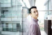 Uomo casual asiatico maturo in piedi da finestra — Foto stock