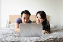 Mature asiatiche coppia casual utilizzando computer portatile nella base — Foto stock