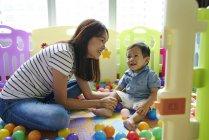 Mãe, uma ligação com o bebê na sala de jogo — Fotografia de Stock