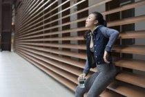 Uma jovem garota asiática está descansando em uma parede após seu treino correndo através dela neigbourhood. Ela está segurando uma garrafa de água. — Fotografia de Stock