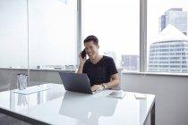 Guapo asiático hombre de negocios hablando por teléfono y utilizando portátil en casa - foto de stock