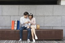 Young asian couple sharing smartphone together — Stock Photo