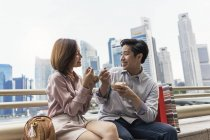 Young asian couple eating food in Singapore — Stock Photo