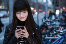 Jolie femme eurasienne regardant son téléphone — Photo de stock