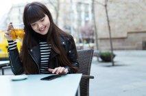 Молодая женщина с длинными волосами просматривает свой смартфон — стоковое фото