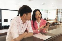 Attractive young asian couple sharing smartphone together — Stock Photo