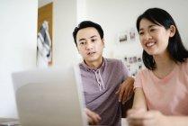 Mature asiatiche coppia casual utilizzando il computer portatile insieme a casa — Foto stock