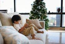 Азіатський сімейні святкування свята Різдва, хлопчик, сидячи на дивані з мобільного телефону — стокове фото