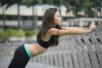 Молодая азиатка растягивается перед бегом в районе залива Марина. . — стоковое фото