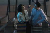 Young casual asian couple with bags at shopping in mall — Stock Photo