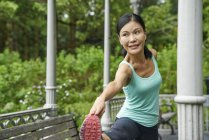 Middle-aged woman warming up in Botanic Gardens before her run — Stock Photo