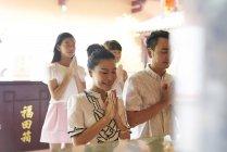 Giovane felice famiglia asiatica pregando nel santuario — Foto stock