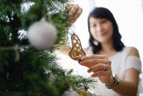 Asian family celebrating Christmas holiday, woman decorating fir tree — Stock Photo