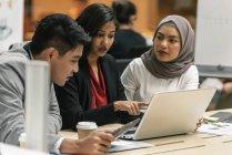 Молодой многокультурного деловых людей, работающих с цифровыми устройствами в современном офисе — стоковое фото
