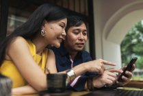 Heureux jeune couple asiatique, à l'aide de smartphone dans café — Photo de stock