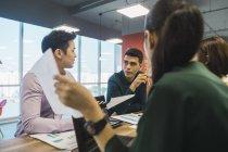 Jovens empresários asiáticos na reunião no escritório moderno — Fotografia de Stock