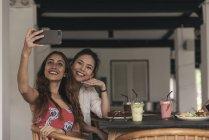 Две молодые красивые азиатские женщины делают селфи в кафе — стоковое фото