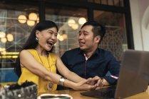 Glückliche junge asiatische Paar mit Laptop und Lachen im café — Stockfoto