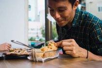 Young asian man eating in comfortable bar — Stock Photo