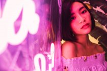 Young asian woman posing beside neon in comfortable bar — Stock Photo