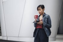 Young Singaporean Malay lady enjoying herself with a cup of coffee outdoors. — Stock Photo