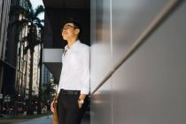 Successful young businessman standing by wall — Stock Photo