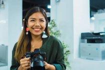Молодая азиатская деловая женщина с камерой в современном офисе — стоковое фото