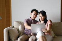 Mature asiatiche coppia casual utilizzando computer portatile a casa — Foto stock