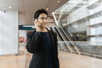 Jovem asiático empresário com bagagem e smartphone no aeroporto — Fotografia de Stock