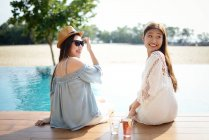 Beautiful young asian women relaxing near pool — Stock Photo