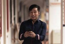 Feliz asiático joven hombre usando smartphone - foto de stock