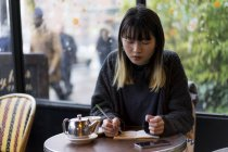 Young attractive casual asian woman writing notes in cafe — Stock Photo