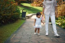 Cute asian mother and daughter walking in park together — Stock Photo