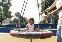 Jovem mãe com asiático filha no playground — Fotografia de Stock