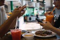 Молода пара їжі в кафе і використання смартфонів — стокове фото