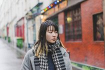 Young attractive casual asian woman on city street — Stock Photo