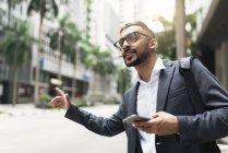 Joven exitoso hombre de negocios con teléfono inteligente y la captura de cabina - foto de stock
