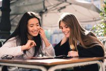 Beautiful friends looking a map in the streets of Spain sitting in a cafeteria — Stock Photo