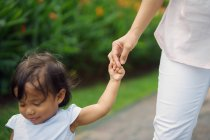 Carino asiatico madre e figlia holding mani in parco — Foto stock