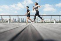 Asian couple running outdoors — Stock Photo