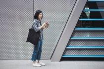 Jovem linda menina asiática em roupas casuais usando smartphone nas ruas da cidade — Fotografia de Stock
