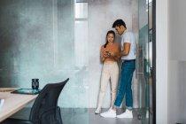 Молодих дорослих бізнесменів за допомогою смартфона в сучасному офісі — стокове фото