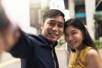 Feliz jovem asiático casal tomando selfie juntos — Fotografia de Stock