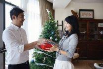 Азіатські сімейні святкування свята Різдва, чоловік одержання подарунку жінка — стокове фото