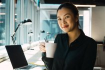 Young adult business woman with coffee cup — Stock Photo
