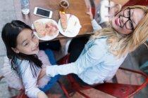 Щасливі молода мати з дочкою, дивлячись на камеру — стокове фото