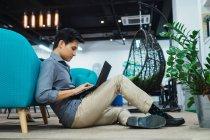 Homem de negócios asiáticos jovens usando laptop no escritório moderno — Fotografia de Stock