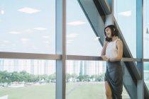 Молоді азіатські ділової жінки говорити на смартфоні у сучасні офісні — стокове фото