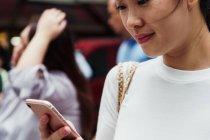 Giovane attraente donna asiatica utilizzando smartphone — Foto stock
